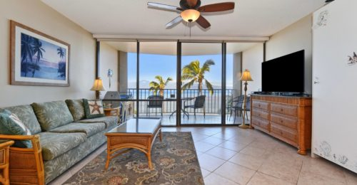 beach condo living room with sliding glass doors and palm trees in background